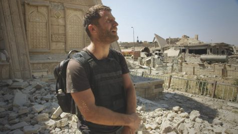 Journalist Ben Anderson stands among bombed ruins in Mosul, Iraq.
