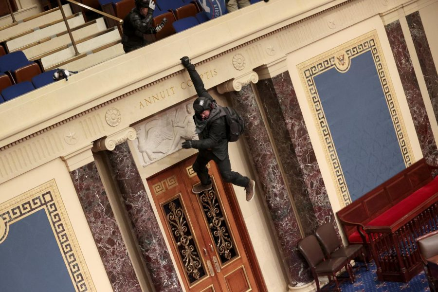 A protester is seen hanging from the balcony in the Senate Chamber on January 06, 2021